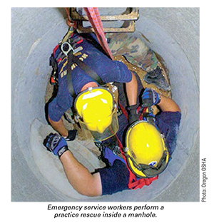 Emergency service workers perform a practice rescue inside a manhole.